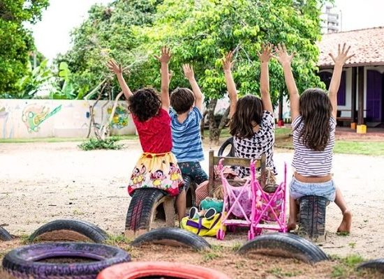 Crianças com as mãos para o alto